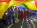 people under giant rainbow flag